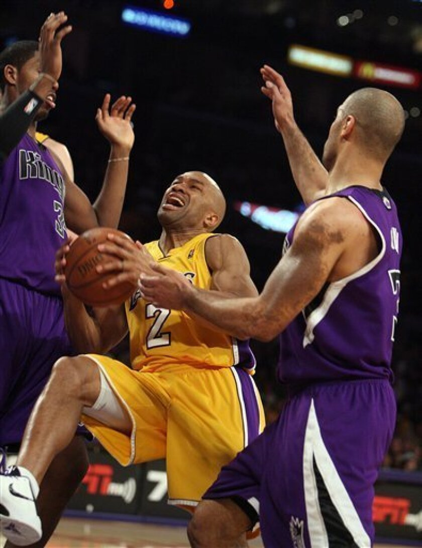 Los Angeles Lakers guard Derek Fisher (2) drives to the basket as Sacramento Kings center Jason Thompson (34), left, and forward Ime Udoka (3), of Slovenia, defend in the first half of an NBA basketball game, Friday, Jan. 1, 2010, in Los Angeles. (AP Photo/Alex Gallardo)