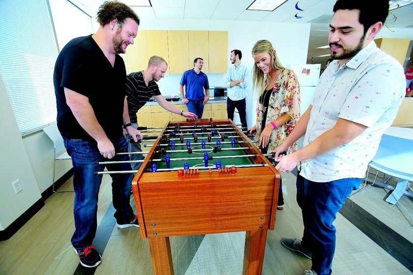 Miva President Rick Wilson (left) plays foosball with Sean Galunas (right) and other employees at company offices in Rancho Bernardo. Nelvin C. Cepeda • U-t