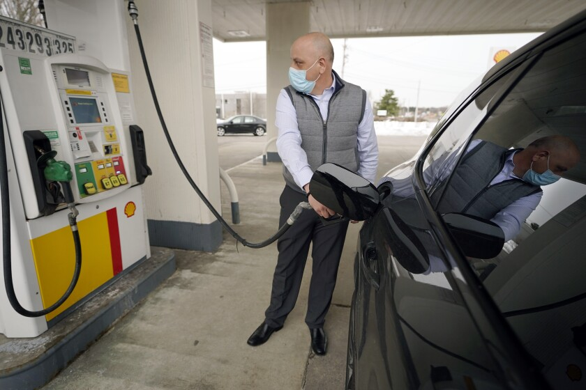 Jeremy Heskett of Boston pumps gasoline at a Shell gas station in Westwood, Mass.