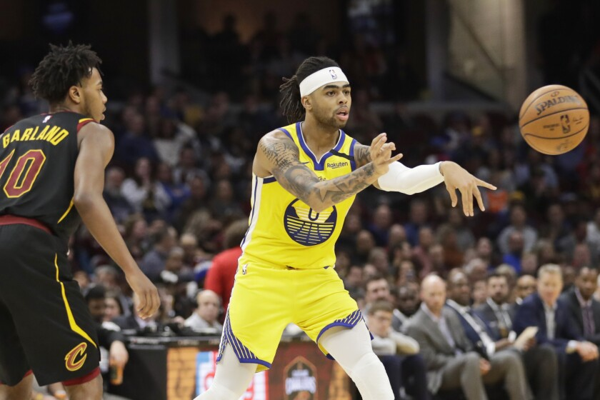 Golden State Warriors' D'Angelo Russell (0) passes as Cleveland Cavaliers' Darius Garland (10) watches in the second half of an NBA basketball game, Saturday, Feb. 1, 2020, in Cleveland. (AP Photo/Tony Dejak)