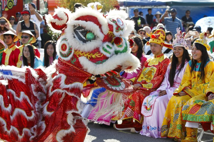 Teens in costume watch the lion dance during the Lunar New Year Festival 2015 at the Qualcomm Stadium parking lot in San Diego on Saturday.