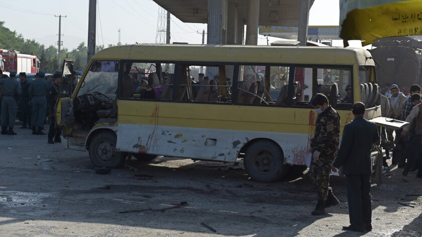 Afghan police look at the site of a suicide attack where a minibus carrying foreign security guards was targeted.
