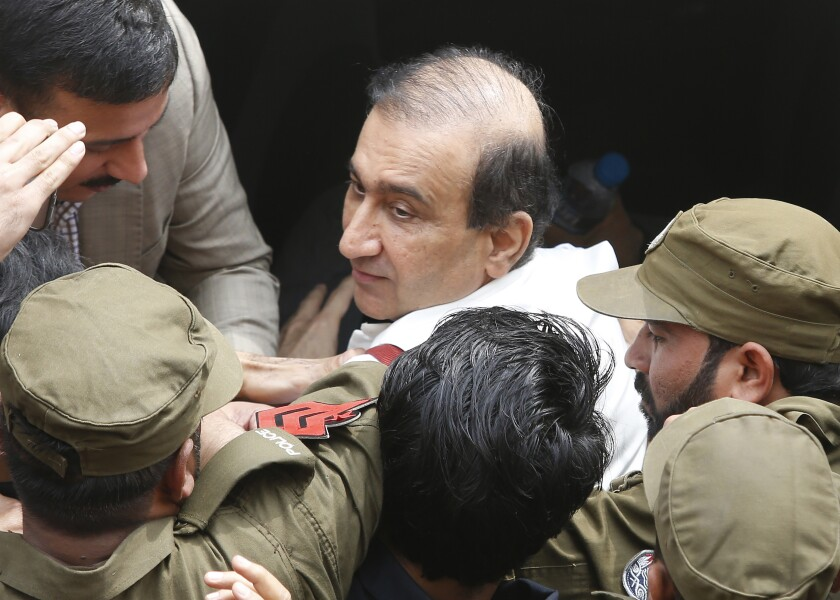 Pakistani police officers escort Mir Shakilur Rehman owner of Jang Group of Newspapers to an anti-graft court in Lahore, Pakistan, Friday, March 13, 2020. Pakistan's anti-graft body Thursday ordered the arrest of the owner and editor-in-chief of Pakistan's largest independent group of newspapers and TV stations in a decades-old case related to allegations of tax evasion in a real estate purchase. (AP Photo/K.M. Chaudhry)