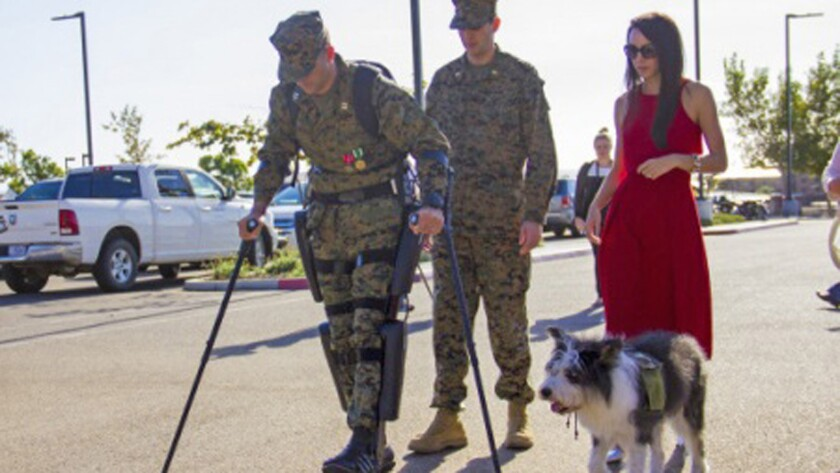 Paralyzed Marine Derek Herrera walks with help of robotic leg braces at a ceremony at Camp Pendleton.