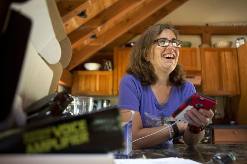 In this Friday, June 24, 2016, photo, Jessie Levine smiles as she listens to her recorded outgoing phone message on her iPhone in Springfield, N.H. Levine was diagnosed with Lou Gehrig's disease or ALS in 2015, and it has caused her speech to become slow and slurred. She is now exploring a new way