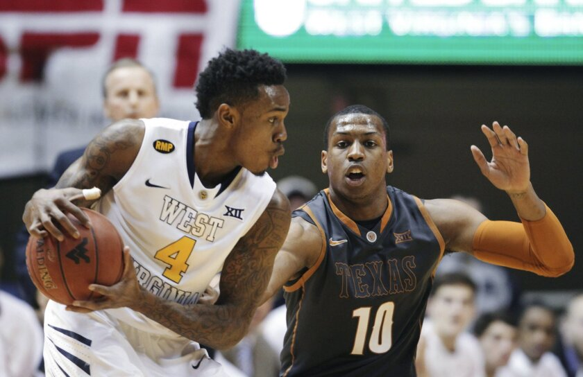West Virginia guard Daxter Miles Jr. (4) looks to make a pass as Texas forward Jonathan Holmes (10) defends during the first half of an NCAA college basketball game, Tuesday, Feb. 24, 2015, in Morgantown, W.Va. (AP Photo/Raymond Thompson)