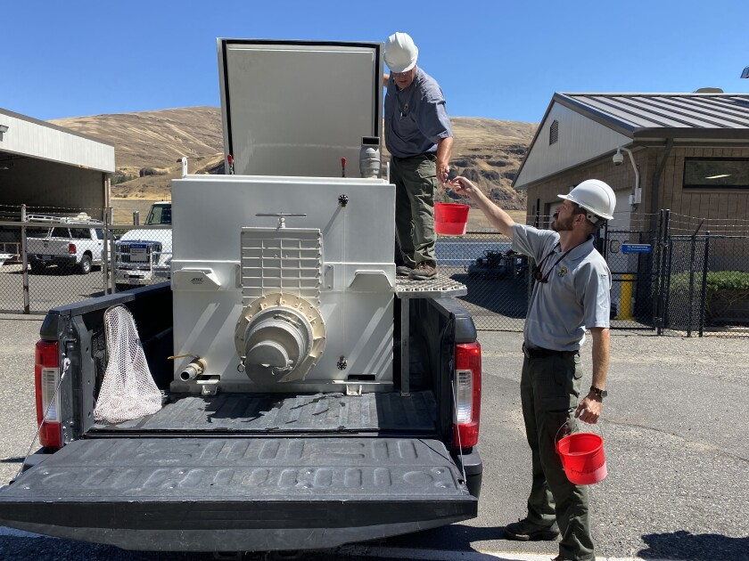 Men in hard hats hold buckets next to a pickup truck with a tank in the bed.
