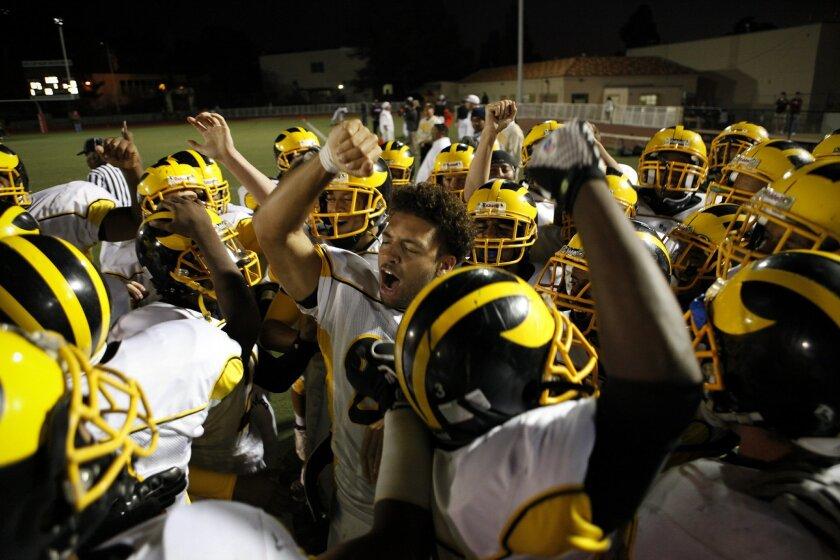 Mission Bay senior quarterback Dillon Baxter (without helmet) fires up his teammates before the Buccaneers' 54-14 Western League road win last night over the La Jolla Vikings. (John R. McCutchen / Union-Tribune)