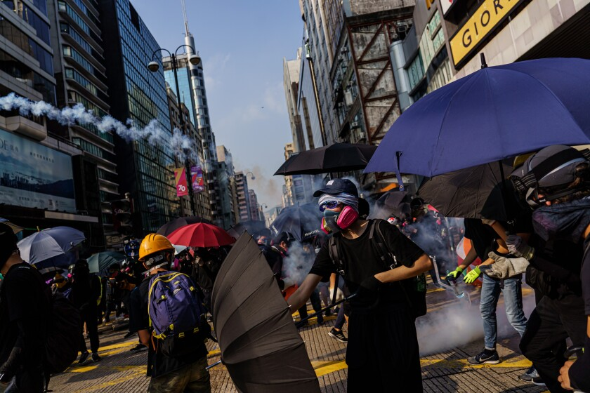 Protesters dodge tear gas canisters