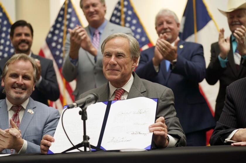 Texas Gov. Greg Abbott holds a voter suppression bill.