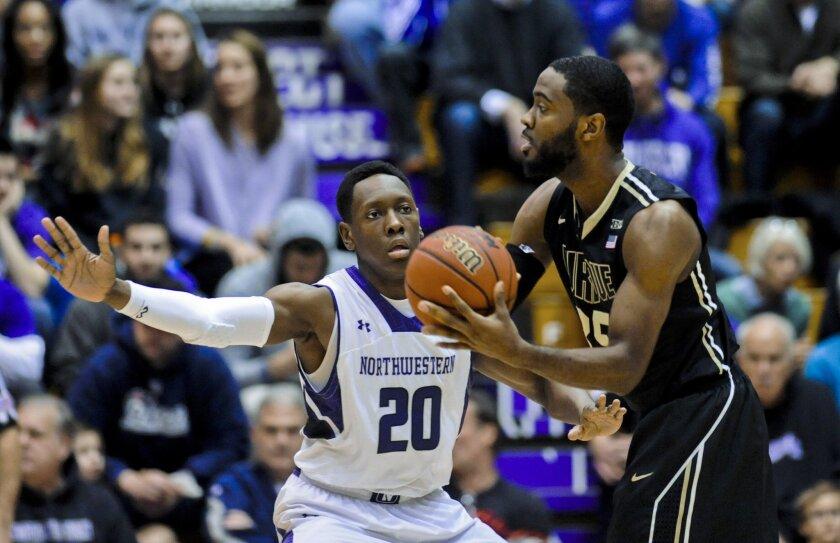Northwestern guard Scottie Lindsey (20) defends Purdue guard Rapheal Davis (35) during the first half of an NCAA college basketball game Saturday, Jan. 31, 2015, in Evanston, Ill. (AP Photo/Matt Marton)