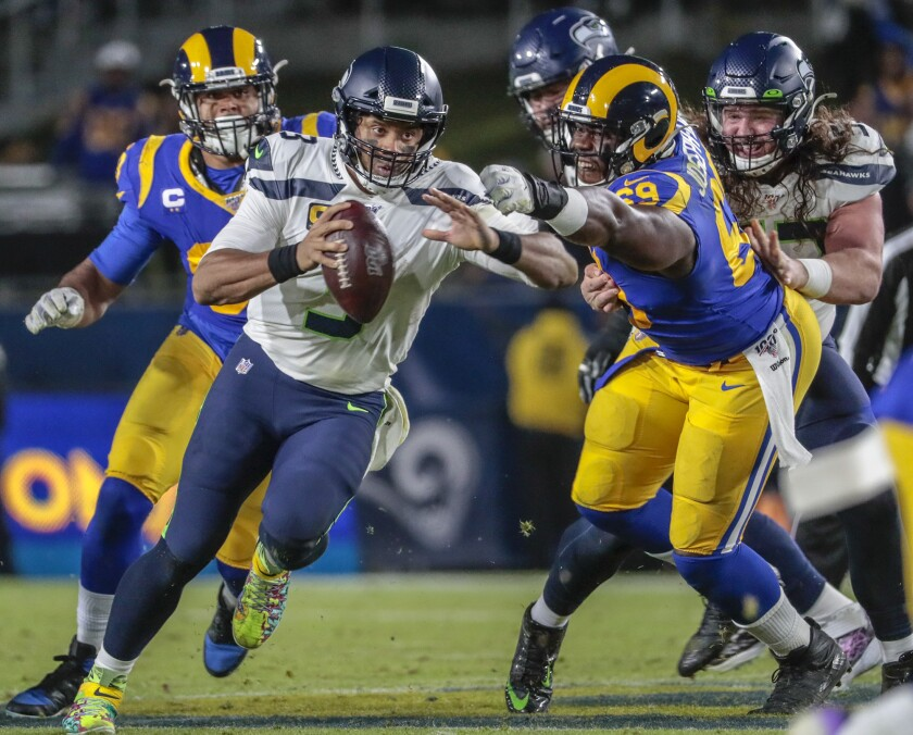 Seattle Seahawks quarterback Russell Wilson (3) scrambles past the Rams' pass rush in December 2019.