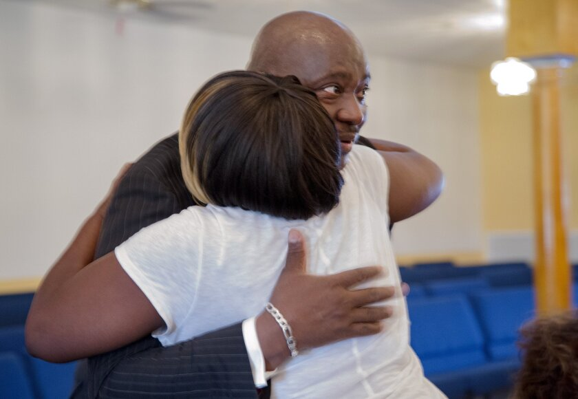 Rosetta Lewis hugs Terry Banks after he spoke about his nephew Corey Jones at a news conference at the Bible Church of God in Boynton Beach, Fla., Wednesday, June 1, 2016. Fired officer Nouman Raja was arrested Wednesday and charged with attempted murder and manslaughter in the Oct. 18, 2015, death