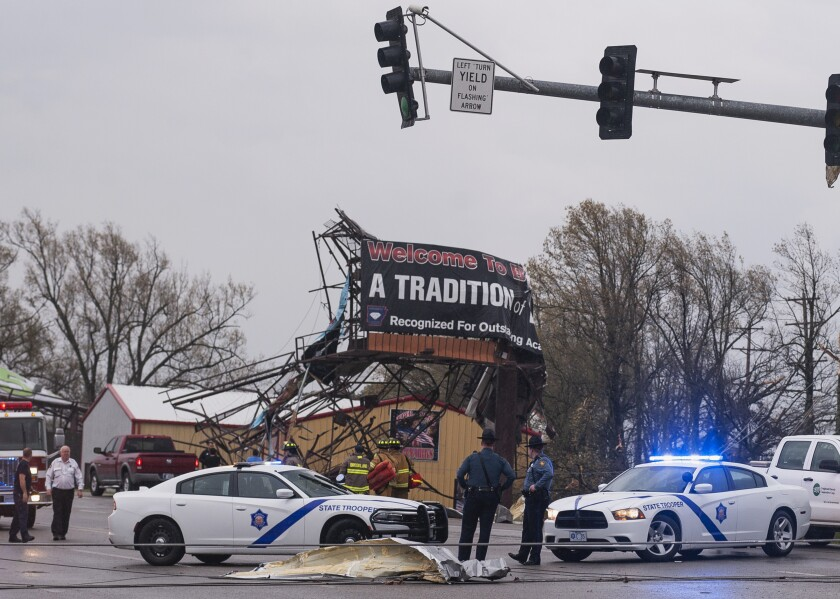 Arkansas State Police and other first responders survey tornado damage in Jonesboro, Ark., on Saturday.
