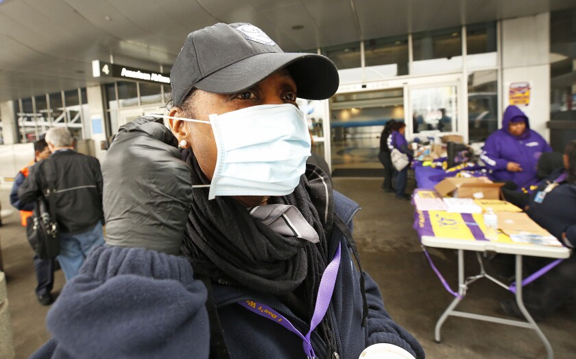 LAX worker dons a face mask