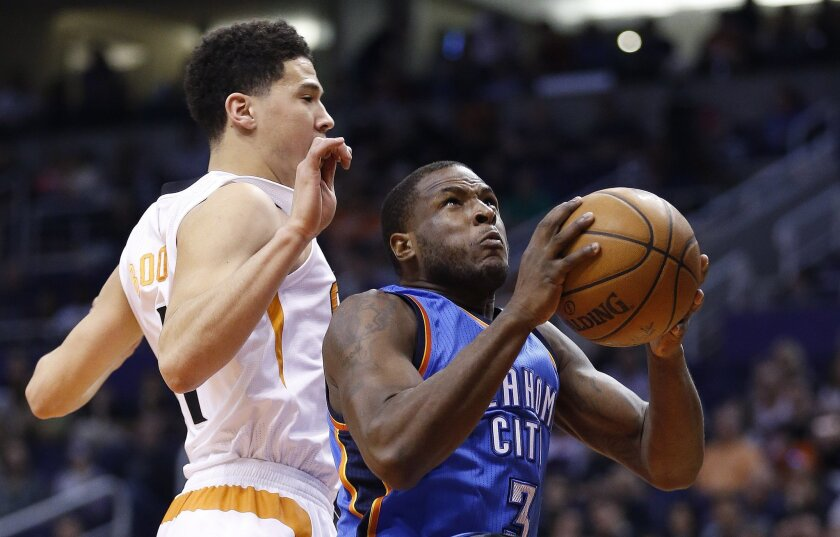 Oklahoma City Thunder's Dion Waiters (3) drives past Phoenix Suns' Devin Booker, left, for a dunk during the first half of an NBA basketball game Monday, Feb. 8, 2016, in Phoenix. (AP Photo/Ross D. Franklin)