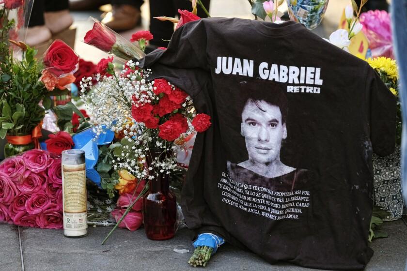 Una camiseta, flores y velas rodean la estrella de Juan Gabriel en el Paseo de la Fama de Hollywood el lunes 29 de agosto del 2016, en Los Angeles. El cantante y compositor mexicano, un ícono de la música latina, murió el domingo en Santa Mónica, California. Tenía 66 años. (AP Foto/Richard Vogel)