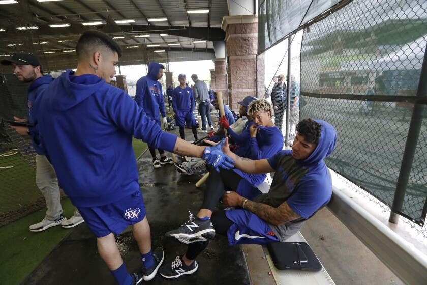 Texas Rangers minor league players Chris Seise, right, and Kevin Mendoza greet one another at spring training on March 12.