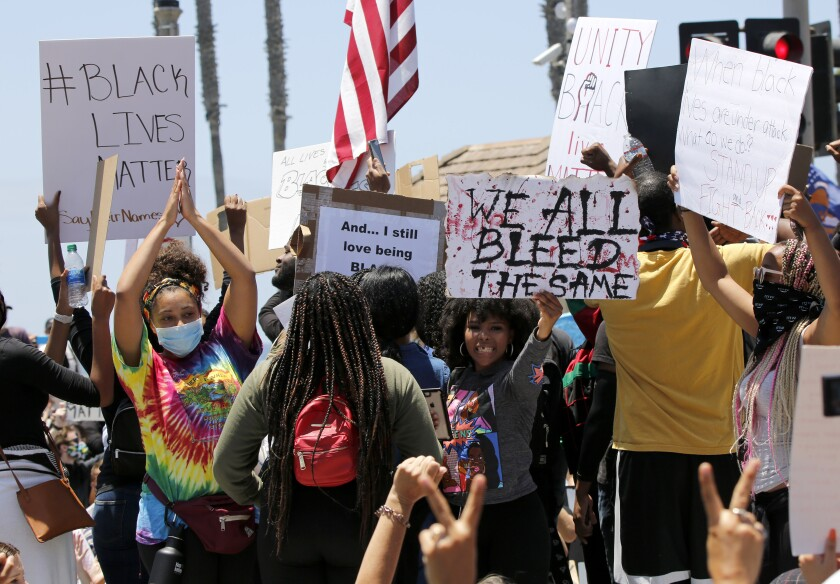 Protesters hold up signs during a Black Lives Matter protest on Main Street and Pacific Coast Highway in Huntington Beach.