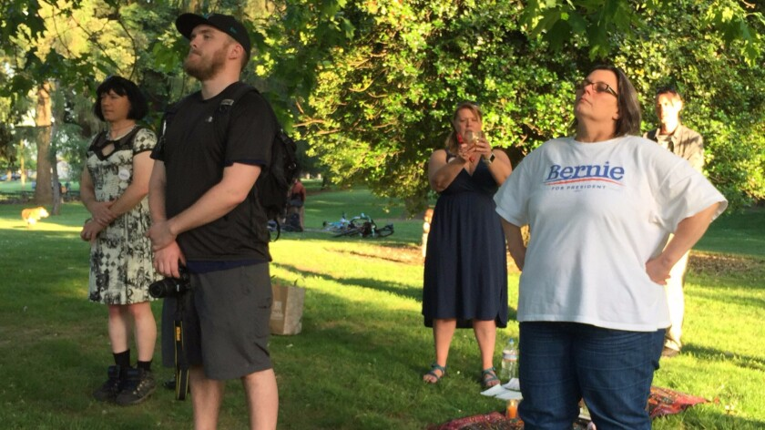 Leigha Lafleur, holding a candle, leads a Wiccan ritual to support Democratic presidential candidate Bernie Sanders on Friday in Portland.