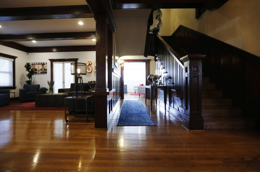 The entrance to Cassandra Corum and Shannon Reese's 1910 Craftsman home in Koreatown features a dark walnut grand staircase.