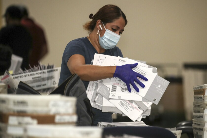 Election worker Yolanda Lavayen carries recall ballots at the L.A. County registrar's satellite office in Pomona.