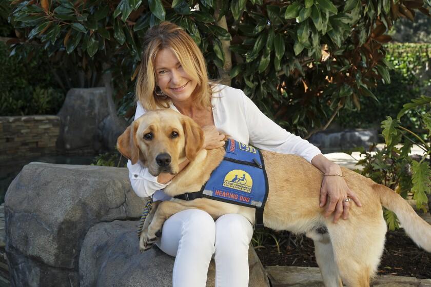 Newport Beach resident Lisa Westerhout, 48, with hearing dog Arrow, her 3-year-old yellow Labrador/Golden Retriever mix.