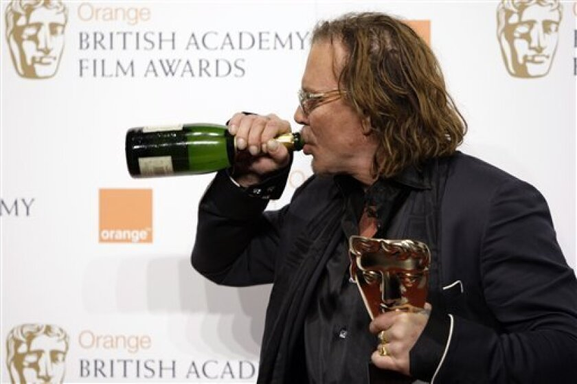US actor Mickey Rourke drinks from a bottle of champagne as he holds his award for Best Actor for his role in 'The Wrestler' at the British Academy Film Awards 2009 at The Royal Opera House in London, England, Sunday, Feb. 8, 2009. (AP Photo/Joel Ryan)