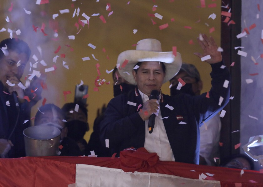 Pedro Castillo waves to supporters after election authorities declared him president-elect