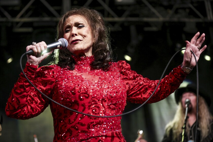 A woman in a red dress sings into a microphone