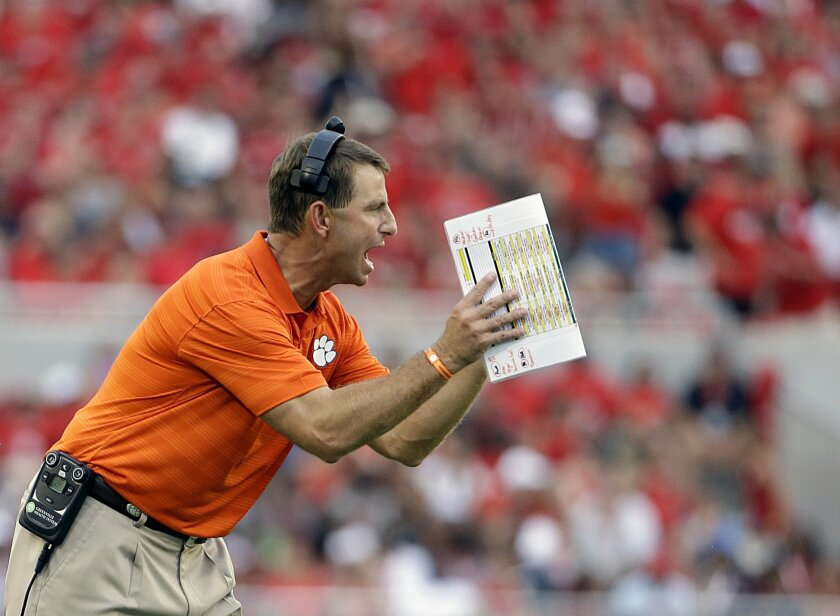Clemson head coach Dabo Swinney talks to players on the field in the first half of an NCAA college football game against Georgia, Saturday, Aug. 30, 2014, in Athens, Ga. Georgia won 45-21. (AP Photo/David Goldman)