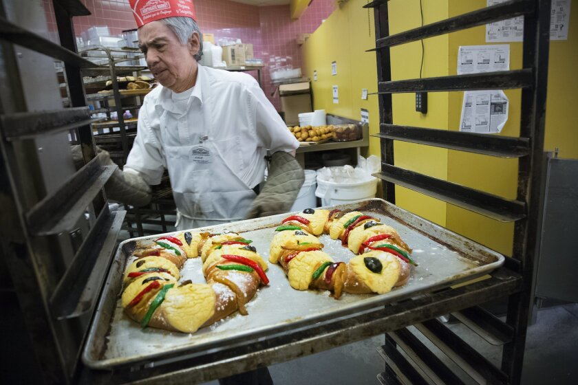 Josue Flores removes rosca de reyes from the oven at Northgate González supermarket.