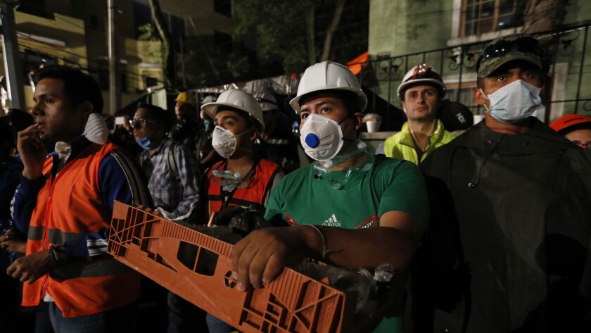 Volunteers await news as rescue teams look for people trapped beneath the rubble of a six-story resi