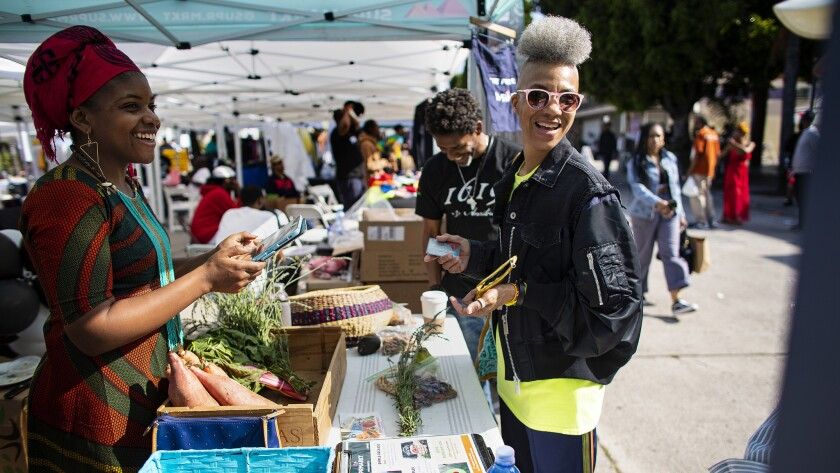 Olympia Auset, left, owner and founder of Süprmarkt, sells groceries to customers in Leimert Park Village on June 15, 2019.