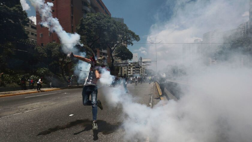 A protester throws back a tear gas grenade launched by police during a street clash Saturday in Cara