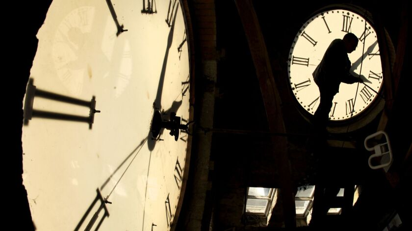 Custodian Ray Keen checks the time on a clock face after changing the time on the 97-year-old clock