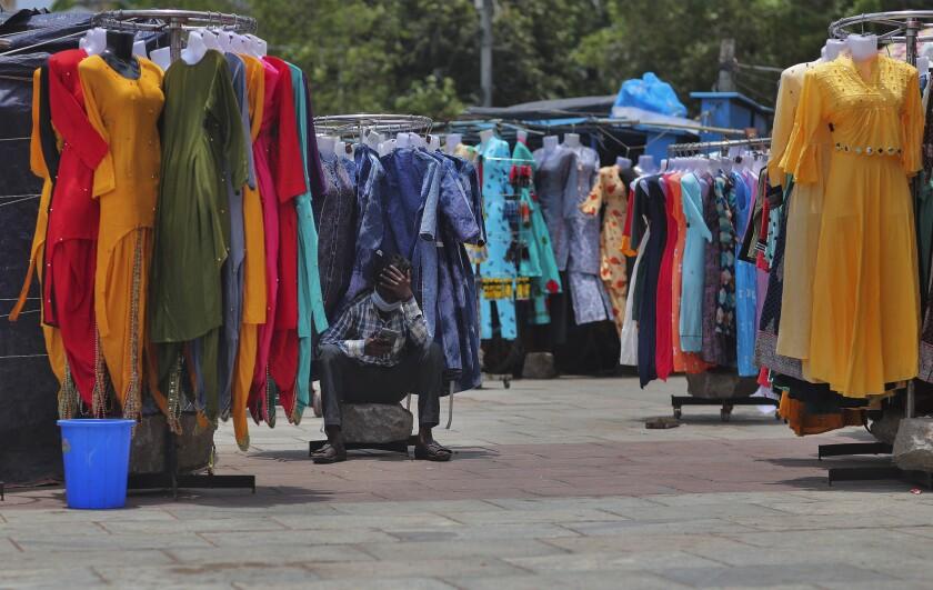 Un vendedor de telas aguarda clientes en Hyderabad, India, martes 7 de julio de 2020. India superó en la fecha 20.000 muertes de coronavirus. (AP Foto/Mahesh Kumar A.)