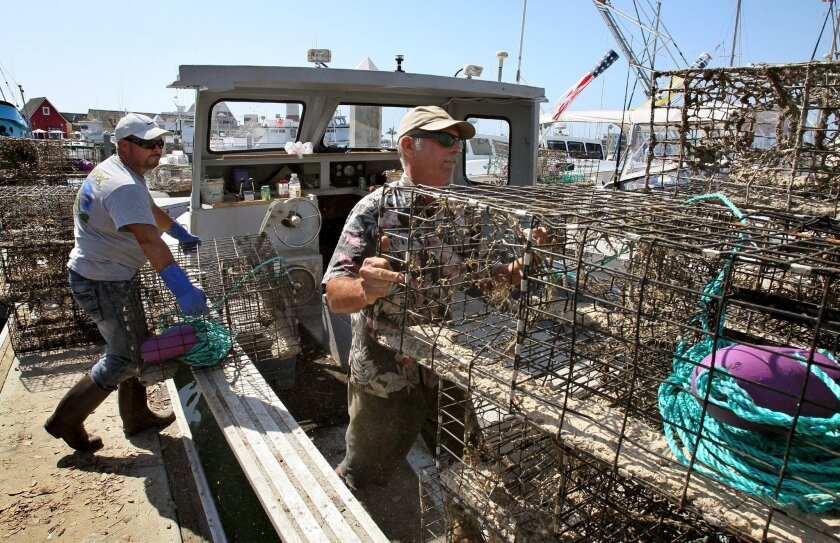 Workers load lobster traps onto a boat at the Oceanside harbor in September.