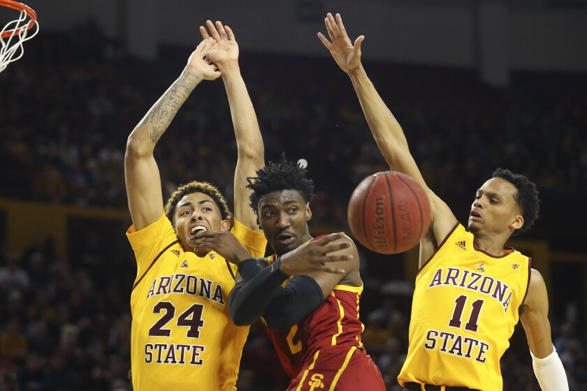 USC guard Jonah Mathews passes after driving against Arizona State's Jalen Graham (24) and Alonzo Verge Jr. on Feb. 8, 2020, in Tempe.