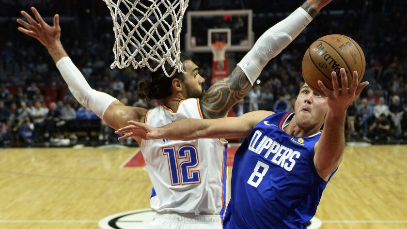 Clippers forward Danilo Gallinari slips past Thunder center Steven Adams for a layup during the second half Friday night.