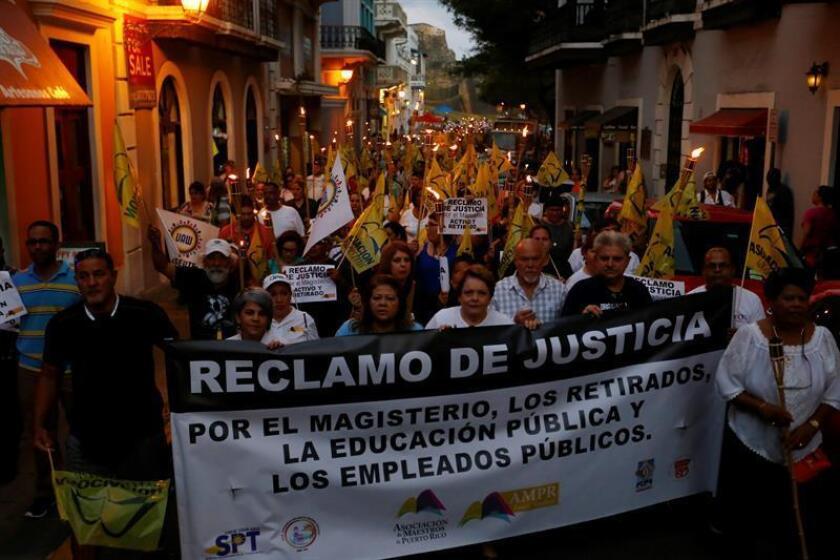 Miembros de sindicatos y la Asociación de Maestros de Puerto Rico marchan, el viernes 17 de marzo de 2017, desde la casa de la leyes hasta La Fortaleza, sede del ejecutivo, en rechazo por los recortes aprobados por la Junta de Control Fiscal, en San Juan (P. Rico). EFE/Archivo