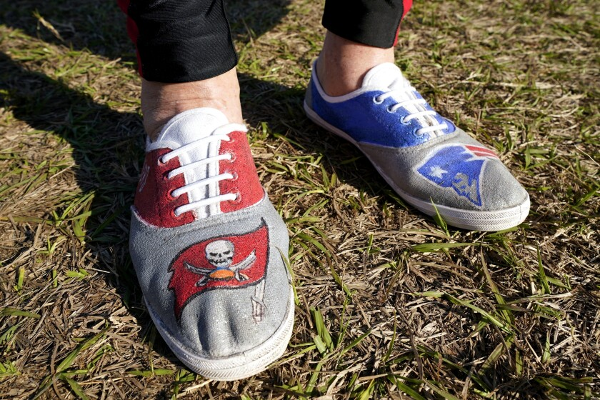 FILE - A fan arrives wearing shoes from both Tampa Bay Buccaneers quarterback Tom Brady's teams before the NFL Super Bowl 55 football game between the Kansas City Chiefs and Tampa Bay Buccaneers in Tampa, Fla., in this Sunday, Feb. 7, 2021, file photo. Brady hasn't played an NFL football game in New England since Jan. 4, 2020. But remnants from his 20-year run with the Patriots remain everywhere in Foxborough. With Brady's new Tampa home just as rabid about the player who brought it a championship in Year 1, it's created a tug-of-war between the fan bases as he gets set to return to the place where his career began. (AP Photo/Mark Humphrey, File)