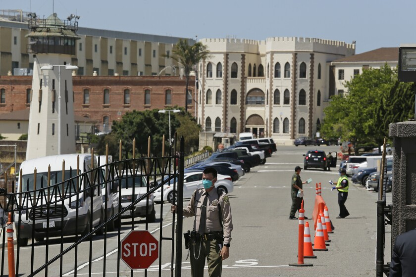 """FILE - In this July 9, 2020, file photo, a correctional officer closes the main gate at San Quentin State Prison in San Quentin, Calif. California prison officials did a poor job requiring inmates and staff to wear masks to slow the spread of the coronavirus, and even """"perplexingly loosened"""" their policy just as cases were spiking, the state's inspector general said Monday, Oct. 26, 2020. (AP Photo/Eric Risberg, File)"""
