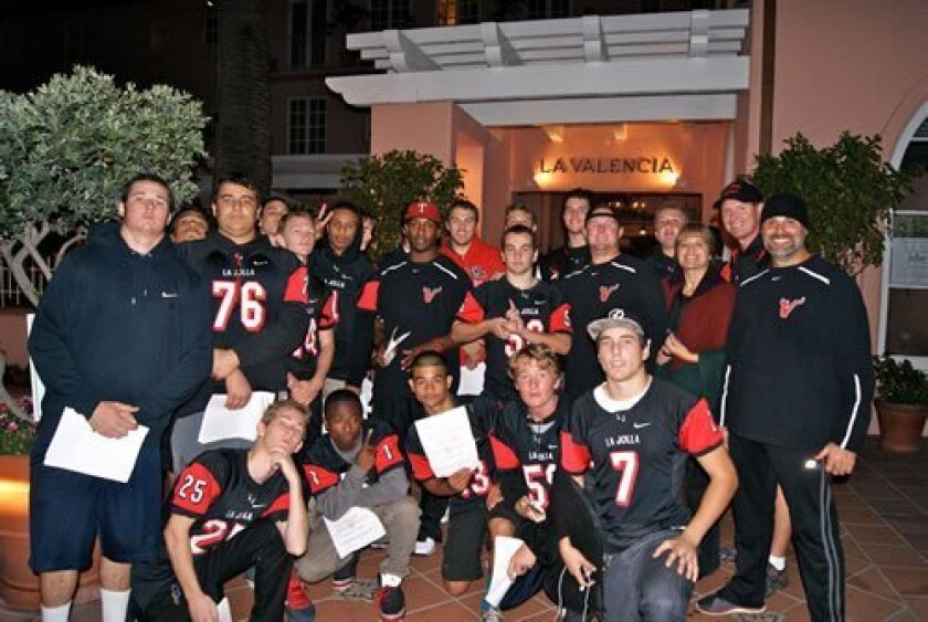 La Jolla High School's Head Football Coach Jason Carter (center, red cap) is surrounded by players, parents and coaches Tyler Roach, John McColl and Craig Gagliardi in front of La Valencia Hotel while handing out flyers to local business. Courtesy