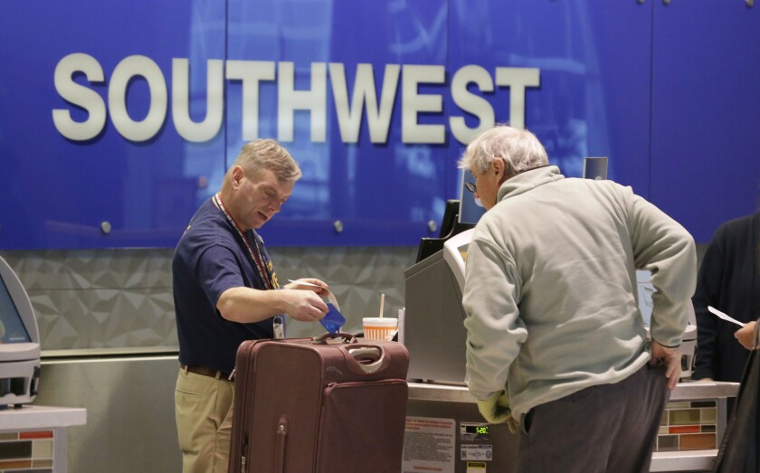 A passenger checks in luggage at the Southwest Airlines counter at Love Field in Dallas. The airline has announced changes to its Rapid Rewards program, making the points vary by flight.