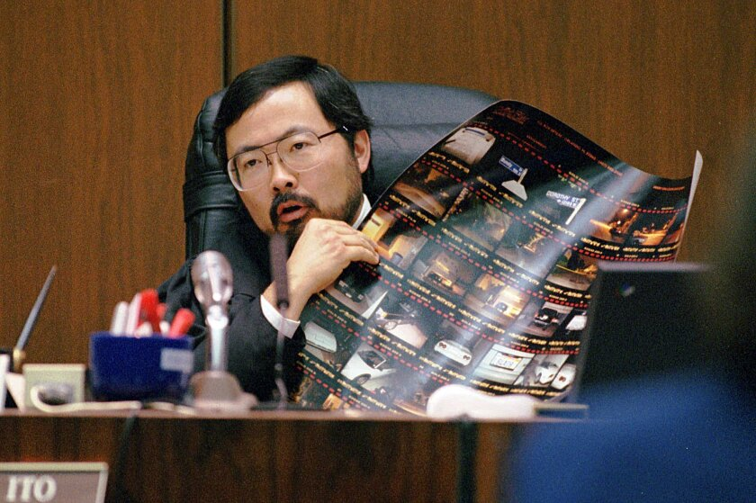 FILE - In this Sept. 7, 1995 file photo, Judge Lance Ito holds up an enlarged proof sheet of crime scene photos during O.J. Simpson's double-murder trial in Los Angeles. In 2014 Ito is still on the Los Angeles Superior Court bench. (AP Photo/Fred Prouser, Pool, File)