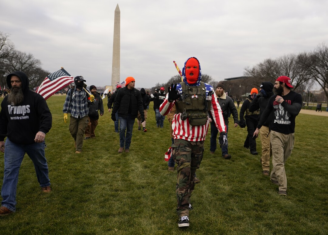 People march on grass with those who claim they are members of the Proud Boys with the Washington Monument behind them.