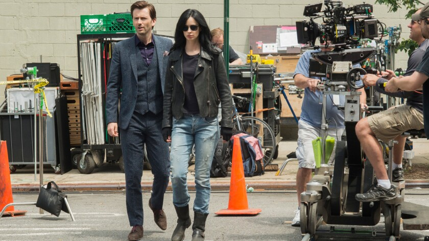 "David Tennant and Krysten Ritter on set during the first season of the Netflix original series ""Marvel's Jessica Jones."""
