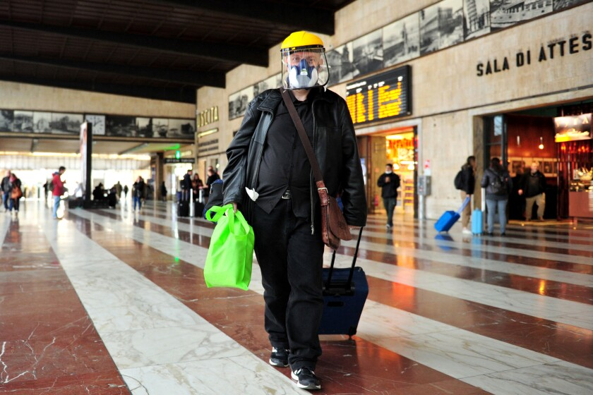 A man wears a mask as he walks in the train station in Florence, Italy, Tuesday, March 10, 2020. Italy entered its first day under a nationwide lockdown after a government decree extended restrictions on movement from the hard-hit north to the rest of the country to prevent the spreading of coronavirus. (Jennifer Lorenzini/LaPresse via AP)