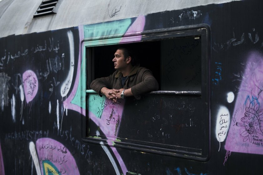 In this Saturday, May 7, 2016 photo, a man looks out of a window of a train that he lives in the sprawling refugee and migrant tent city of Idomeni, on Greece's northern border with Macedonia. After refusing to move for months, refugees camped out at the Greek border were bused to shelters in a pol